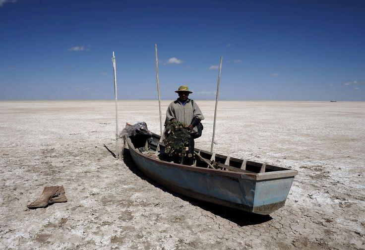 Fiskeren Rene Valero på båten sin ved den uttørkede sjøen.