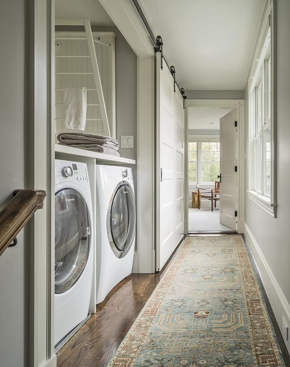 Chic Hallway Laundry Room Features A Sliding Barn Door On Rails