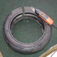 Autobanden bewerken tot meubilair, doorsnijden van het rubber.