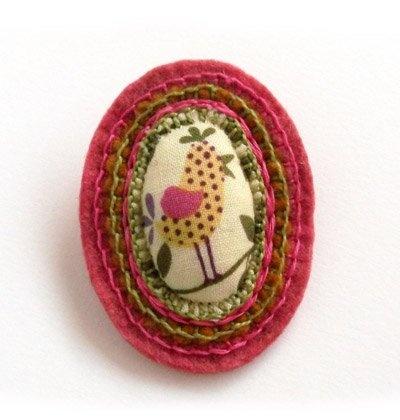 Nyurga madárka textilkitűző  Madárka mintás textil és filc felhasználásával készített kitűző. Erőteljes rózsaszín, zöld és sárga színekben pompázik.