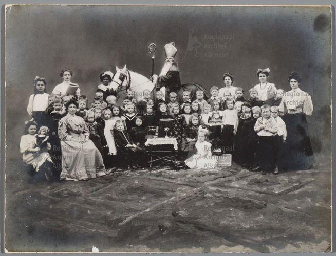 """Sint Nicolaas op de fröbelschool aan de Doelenstraat . Groep kinderen met hun onderwijzeressen met daarachter Sinterklaas op zijn paard dat vastgehouden wordt door Zwarte Piet. Tussen de kinderen staat op een tafeltje een klok, bij het tafeltje een schoolbordje met daarop de tekst """"klokje van gehoorzaamheid"""". Het tapijt op de voorgrond is op de foto bijgeschilderd. (1908)"""