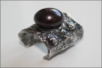 Anillo de plata con acabado de plata arrugada y con una perla negra en el centro.$89 euros. Precio indicado en euros.