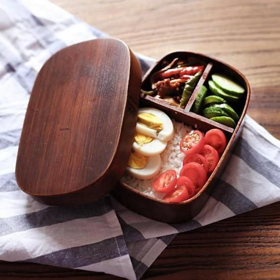Make lunch more awesome for your kids by using this Handmade Wooden Lunch Box. Inspired from Japanese Bento Boxes, these have a special handmade design that looks sophisticated and pretty stylish for everyday use. The box comes with slots that will help you to serve lunch in a proper way. The wood used is eco-friendly and perfect to serve as a lunch-box. It's what you will love serving lunch in for your family members, be it kids or your spouse. After all, a Handmade Wooden Lunch Box is n...