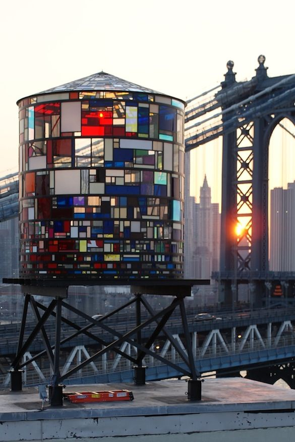 DUMBO |||||| Tom Fruin's renowned Watertower sculpture is situated in DUMBO, Brooklyn. Watertower is composed of nearly a thousand fragments of plexiglass, all locally scavenged. Catch wonderful views and a beautiful light show of Fruin's artwork from Brooklyn Bridge Park. The original was taken down in June but there is still a replica on the roof. Spot another Fruin-designed watertower at 334 Furman Street in Brooklyn Bridge Park.
