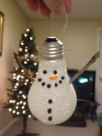 Light bulb covered with mod podge, dipped in white glitter, glue sticks  for arms (cut mittens from felt), black and orange beads for features.