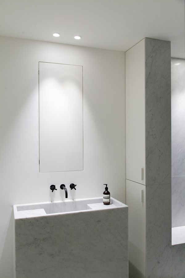 Carrara marble sink + hidden mirror (cabinet) + bold black Hansgrohe tap. Minimal bathroom by Annemarie van Riet.