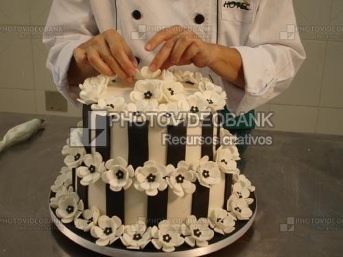 Bolo flores brancas duplo | PHOTOVIDEOBANK confeiteiro decorando bolo flores brancas grandes, dois andares, bolo listrado, bolos decorados com pasta americana, confeiteiro, confeitaria.