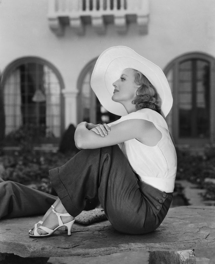Simple elegance- wide legged dark trousers (like the side buttons), sleeveless white blouse top, white strappy sandals and fabulous wide brimmed white hat. Joan Crawford c.1930s.