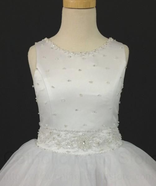 (4 Tea Length, White) This sleeveless First Communion dress has a lovely satin bodice adorned with all over scattered pearls. The neckline is outlined in matching pearl clusters. The stunning waistline is also created with a pearl design and includes sparkling beaded accents. The back of the dress is a mirror image of the front but has faux satin covered buttons that hide the zipper closure. The dress is paired with a princess style sheer overlay skirt that is puckered at the waist for added…