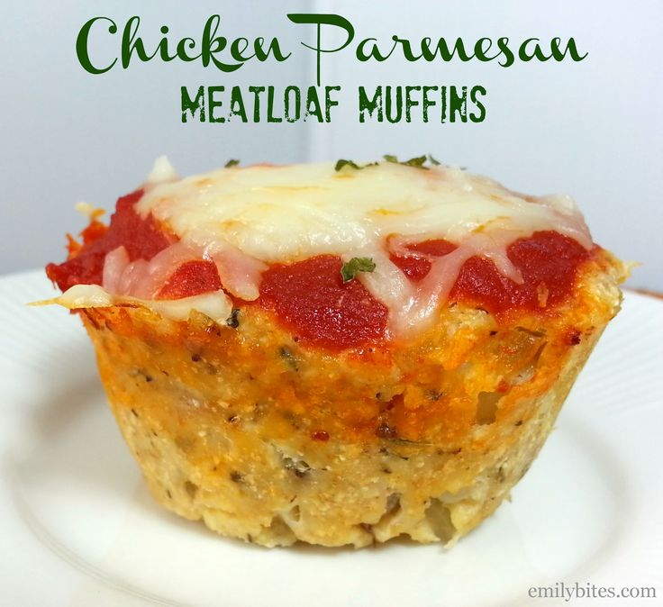 Chicken Parmesan Meatloaf Muffins - 1 ½ lbs raw ground chicken breast,  1 large egg,  1 egg whites,  6 T dried breadcrumbs,  ¾ t dried basil,  ¾ t dried thyme,  ¾ t oregano,  2 garlic cloves,  ½ small onion,  ¾ t salt,  1/3 t black pepper,  ¾ c Parmesan cheese,  ¾ c pasta sauce,  ¾ c 2% reduced fat shredded Mozzarella cheese,  dried parsley, oregano or basil for garnish