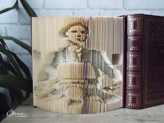 La collection A Livre Ouvert est une série de livres doccasion transformés en objets de décoration via plusieurs techniques (découpage, pliage ou décou-pliage). Chaque page est découpée et/ou pliée à la main pour donner vie à un motif.  Le modèle Lhomme à la moto est un livre découplié qui mesure 20 cm de haut et possède une magnifique couverture bordeaux et or. VENDU SEUL