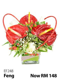 3 anthuriums and 3 roses in a glass vase.