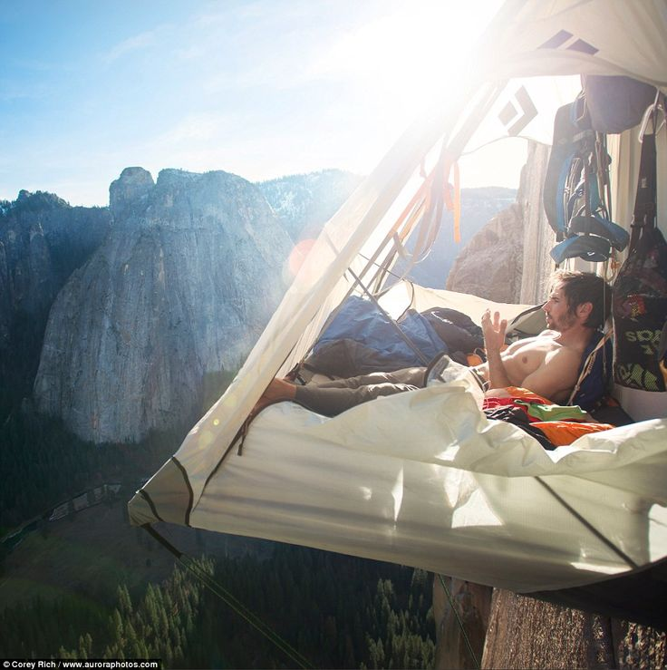 Kevin Jorgeson relaxes in his portaledge tent, which is attached to the rock face and hangs above the Yosemite Valley floor far below