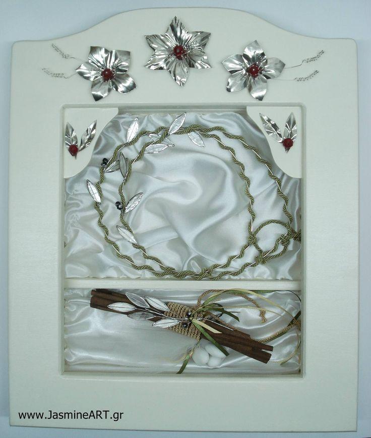 Στεφανοθήκη Αλπακάς  Χειροποίητη ξύλινη στεφανοθήκη σε χρώμα ιβουάρ ή λευκό με χειροποίητα λουλούδια από αλπακά. Η στεφανοθήκη διαθέτει δύο θέσεις, για τη μπομπονιέρα και τα στέφανα. Τιμή:130.00€