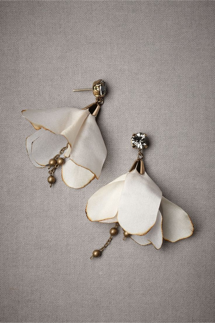 It took me a while, but I finally located and put together materials for earrings similar to these: white silk flowers with purple tips, earring hooks with rhinestones, conical findings, thin chain, balls (6 small for ends of chains, 2 bigger to hold petals in place under cones), and pins.  All metal antiqued.  Love them!