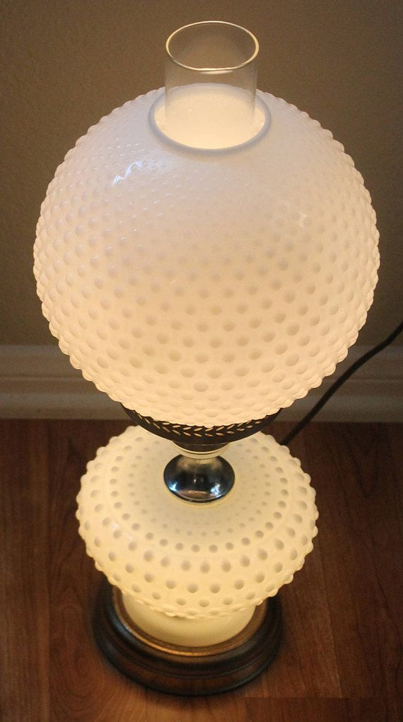 1950s Fenton Hobnail White Milk Glass Globe Table Lamp + Three Different Settings For Light + Gold Trim + 20 inches Tall + 11 inches Wide Top Globe + Gold Base Stand Condition: Good There are a few scratches on the gold trim and base of lamp due to wear and tear No other flaws to