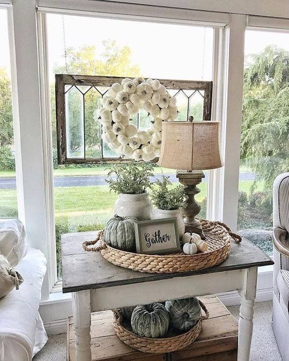 A textured wicker tray looks beautiful with greenery and a rustic lamp as the focus