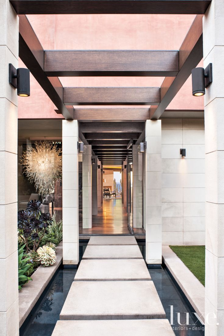 Architect Mark Singer designed a limestone colonnade that passes through the courtyard connecting a separate garage structure with the main house.