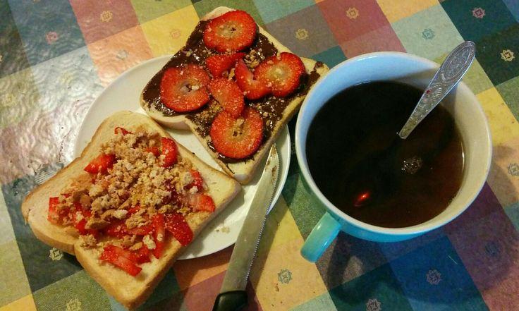 Tè nero e due toast aperti con cioccolato fondente, fragole, amaretti sbriciolati e sciroppo d'acero.