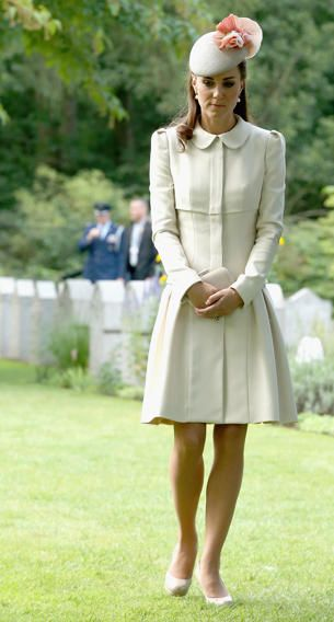 in a custom cream coat dress with a pleated skirt and Peter Pan collar by Alexander McQueen, Catherine, Duchess of Cambridge adds some warmth in her getup to a rather somber event at a cemetery.