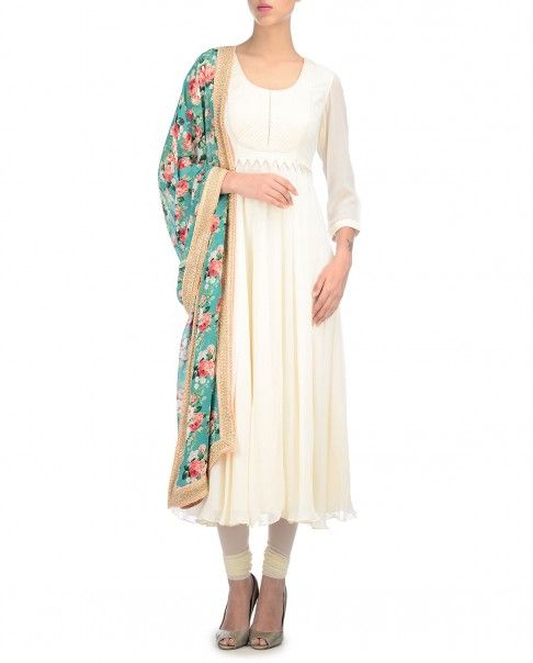 Ivory anarkali kurta with thread stitching accents and geometric charms adorning the yoke. Fish line curly hem. Round neckline. Three quarter sleeves. This suit comes with a floral printed dupatta with golden border. Wash Care: Dry clean onlyMatching churidar leggings included