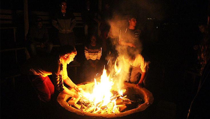 Huddled around, and helping to prepare the camp fire for the evening.