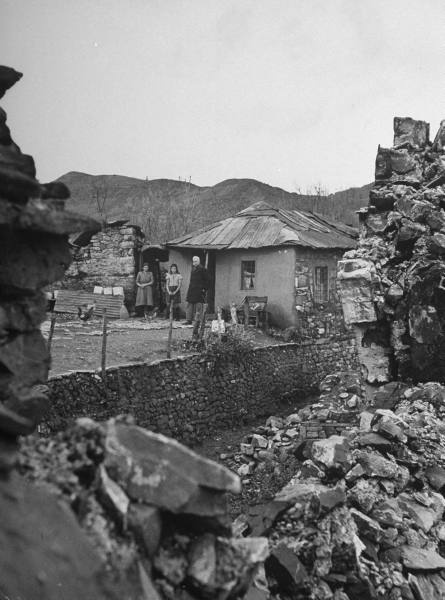 Civil War/Greece  Lt. Col. Economitas (R) standing with his wife and daughter outside of their home.Location:Louzesti, Greece  Date taken:December 1947  Photographer:John Phillips