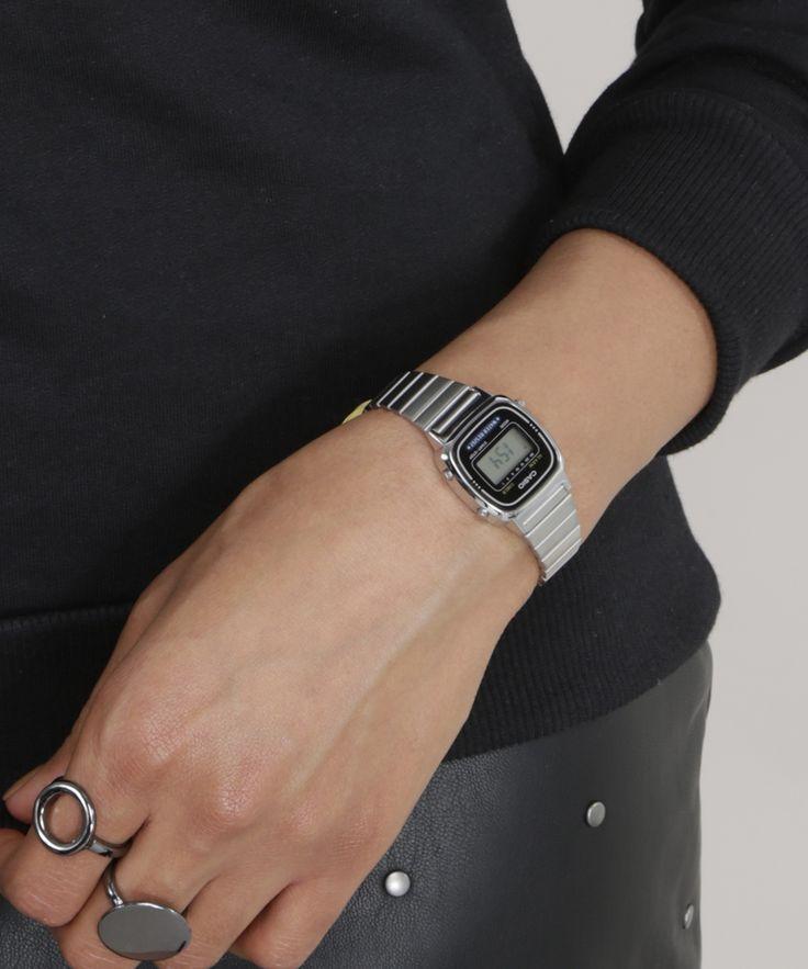 Relógio com pulseira feita em placas metálicas articuladas. A caixa de formato quadrado foi desenvolvida em metal. O visor é digital. A resistência é de 3 ATM, permitindo contato superficial com água enquanto usa a peça.