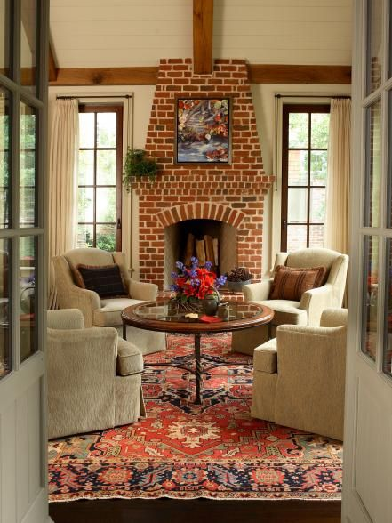 The shape of this fireplace, along with its traditional red brick, gives it a classic look. Brick is a low-maintenance, sturdy material that makes a great insulator. It's routinely salvaged and re-used because of its proven longevity. Design by Elinor Jones