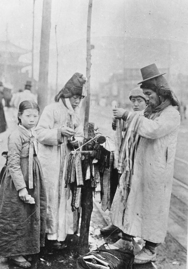 Pyongyang ca 1920s-1930s. Street vendors sell ribbons, ties, cloth strips...?