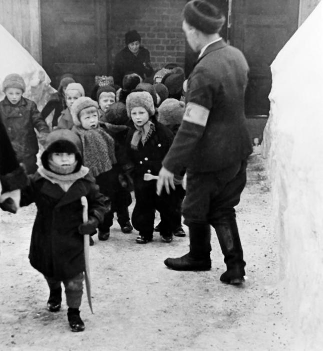 Escorting nursery children from an air raid shelter in 1942