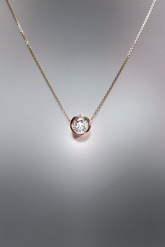 This stunner is composed of a .50 carat solitaire diamond, G SI 1 or better, set in a 14k gold bezel setting and a 16, 14k gold cable chain. Available in
