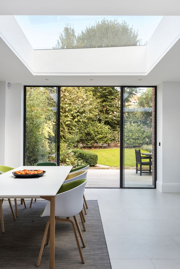 Streatham house - Granit Architects. Light and airy dining area in rear extension. Space flooded with natural light from large rooflights and sliding external doors. Oak and white dining table with colourful chairs. Upholstered chairs with mix matched colours. Tiled flooring with large run beneath table. Beautiful views of the garden.