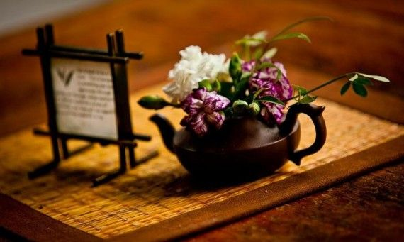 a teapot with flowers and a sign with a meaningful inscription