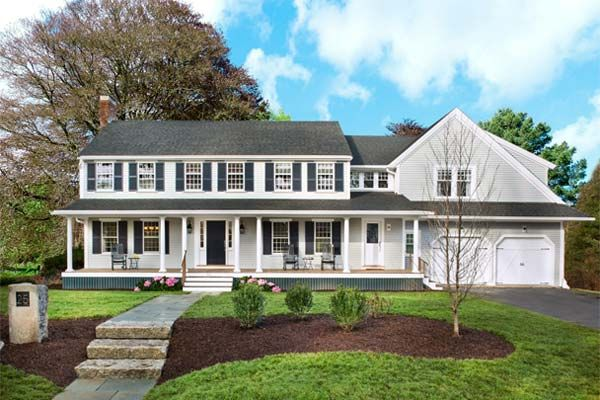A new farmer's porch adds a welcoming element to the front of the The Lexington Colonial house, and its roof ties the old house to the addition above the garage.