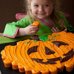 Pumpkin Patch Pull-Apart: From Woman's Day. To create this impressive pumpkin-shaped display, arrange mini carrot cake cupcakes, filled with crushed pineapple and flaked coconut, then top with a silky cream cheese frosting and create a jack-o'-lantern face with chocolate.    The site has the recipe.