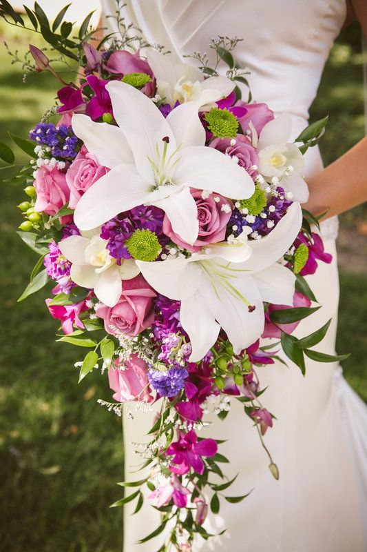 pink and purple takes a back seat to the ginormous white Lilly cluster in this cascading wedding bridal bouquet :: Photo © www.photokisses.com