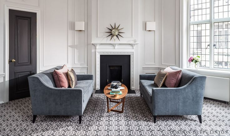 Octagonal meeting room with original fireplace. Dusty blue sofas with pink cushions. Geometric patterned carpet.