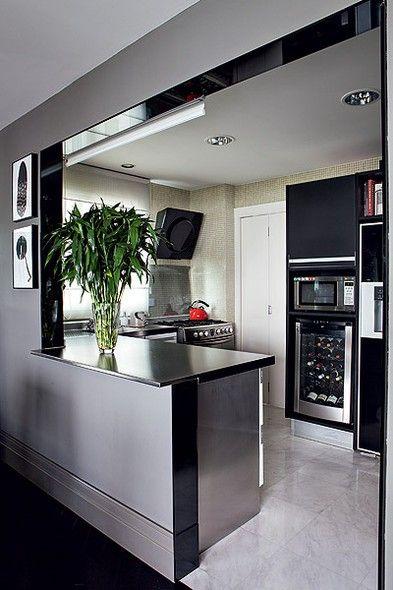 Piso de mármore e paredes revestidas de pastilhas de vidro dão um ar sofisticado e de sobriedade à cozinha americana