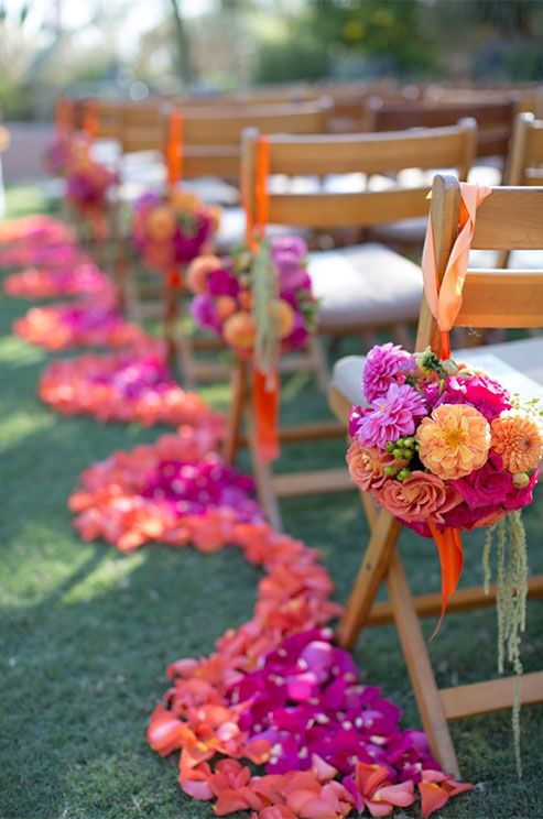 Bold orange and pink blooms make for a dramatic aisle.
