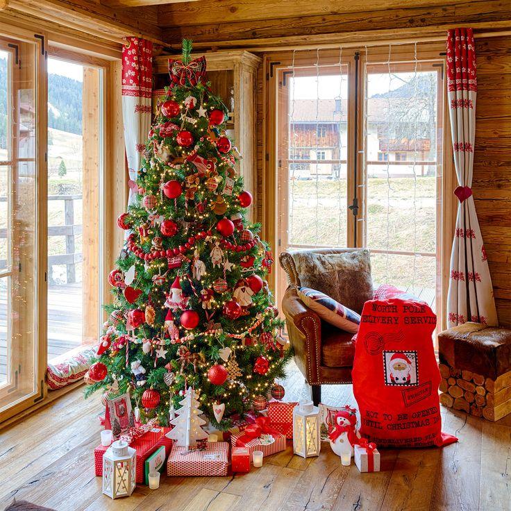 Albero di Natale tradizionale rosso con decorazioni a tema, palline e pacchi regalo con le renne