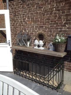 mijn side table in de tuin voorzien van decoratie. Twee kandelaars, 2 ornamenten, een krans, vogelhuisje en een mooie plant met witte bloemen in een rieten mand. Dit alles op mijn side table van een oud tuinhek met steigerhout