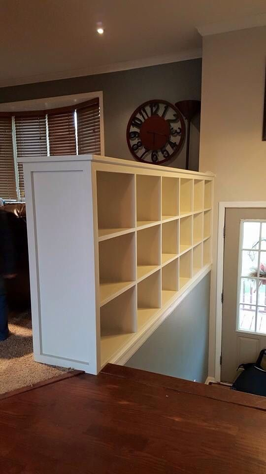 We finally got ride of the typical split level entry way railing and replaced it with a book case for storage- love it!!