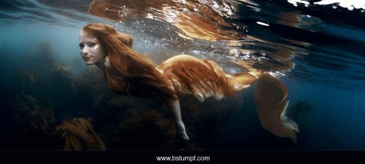 Photo of a redhead mermaid in an orange and yellow tail swimming in the ocean at Catalina Island off the coast of Southern California and Los Angeles. Underwater photography art by Brenda Stumpf. Model Jessica Dru. See more at www.sheroesentertainment.com / www.facebook.com/sheroesentertainment / www.facebook.com/themermaidproject