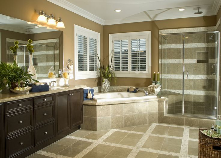 Large bathroom in beige and browns with corner tub and adjacent glass shower