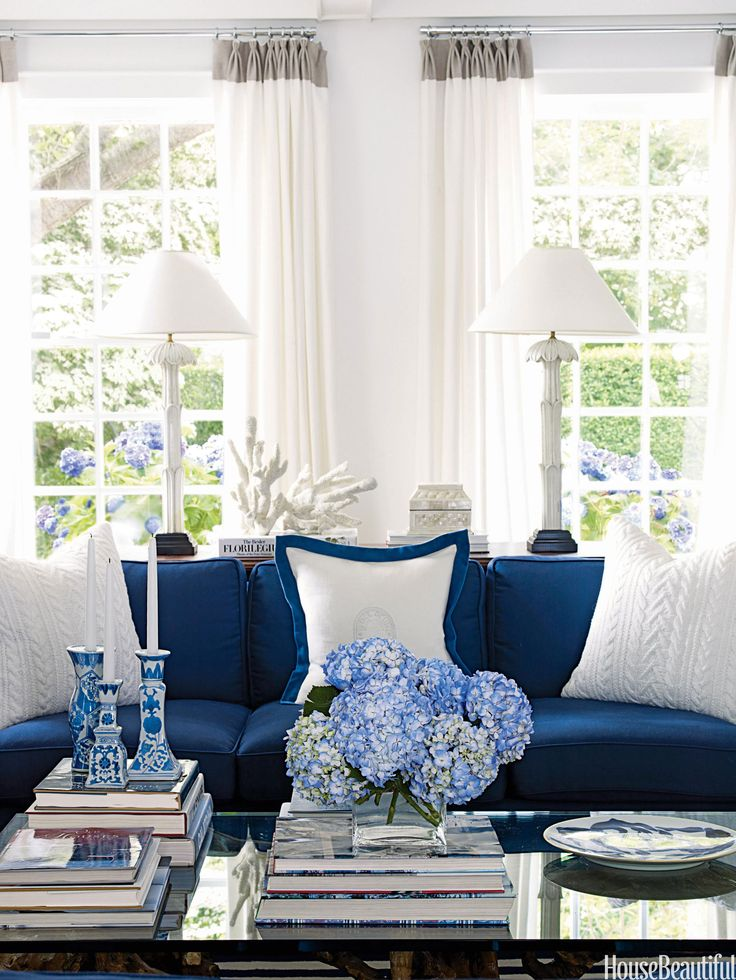 Making a neat pile of books and magazines will bring order to a coffee table in a matter of minutes. For this Hamptons home, designer David Lawrence created a sophisticated tabletop display by placing flowers and candles atop the books. The fabric on the sofa is Vizir in Indigo from Old World Weavers. Throw pillows by Ralph Lauren.   - HouseBeautiful.com