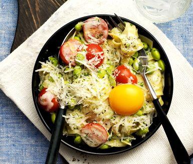 Pasta carbonara på sojabönor, ett gott och enkelt recept. Pasta kokas enligt anvisningar där sojabönor läggs i mot slutet. Lök steks mjuk i en kastrull och grädde, vatten och buljong tillsätts för att koka. Ost vänds ned i pastan för en krämig smak, servera med tomathalvor, resten av osten och äggula.
