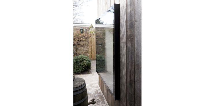 Frameless window in garden retreat.