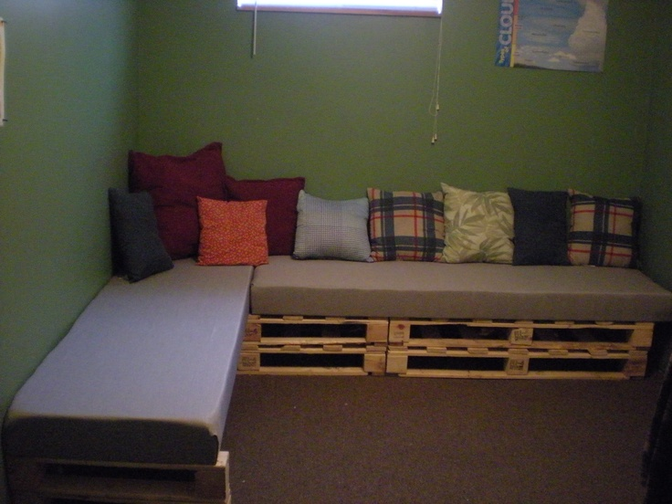 Pallet Sectional Couch.    Made with pallets cut in half then stacked.  Foam twin matresses cut to size from JYSK,   Covered with drapes from Fabricland.    This can be converted to a large bed by moving the end pallet (pictured here with the cushions on it) over beside the other pallet - then take the cushion and put it parallel to the the other mattress.