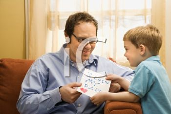 Royalty Free Photo of a Boy Giving His Father a Drawing